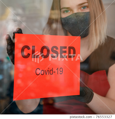 Sign Closed covid 19 lockdown on shop front entrance door as new normal shutdown. Woman in protective medical mask gloves hangs closed sign on window of cafe restaurant. Lockdown Square crop 76553327