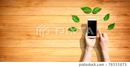 Person holding smartphone with green leaves 76555873