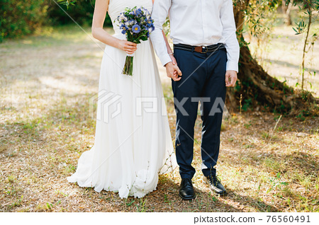 Bride with a bouquet of blue flowers and the groom stand side by side in the olive grove and hold hands 76560491