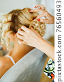Stylist doing hair to blonde bride during preparation for wedding ceremony, close-up  76560493