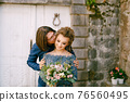 The groom kisses the bride on the cheek against the background of an old building with white doors in the old town of Perast  76560495