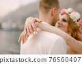 The bride and groom hug on the pier, the bride in a delicate wreath wrapped her arms around the groom's neck 76560497