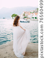 The bride stands on the pier near the old town of Perast and holds the edge of her skirt 76560499