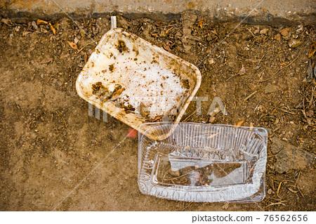 Littering concept. Two plastic packs on bare soil, biodegradable materials 76562656
