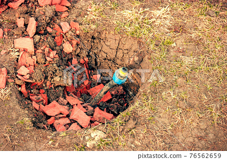 Repair and fixing in yard concept. Broken water pipe in back yard ditch with fragments of red bricks 76562659