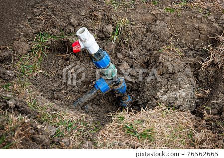 Repair and fixing concept. Busted and broken water pipe back yard 76562665