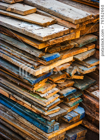 Old planks in stack on backyard 76562668