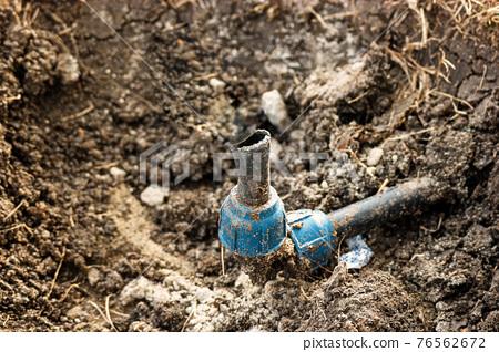 Broken watering pipe inside the ditch 76562672