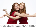 Cheerful mom and daughter next to red dresses hugs lifestyle light background smile 76563802