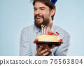 Bearded man with a plate of cake on a blue background and a birthday party hat on his head 76563804