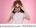 little girl in fashionable glasses and clothespins on her hair emotions pink background hearts 76564639