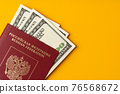 Russian passport with US dollar banknotes inside 76568672