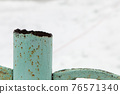 A rusty metal pipe sticks out over an iron fence. 76571340