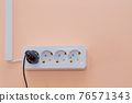 An outlet with a plugged-in plug and wires going side by side in a box 76571343