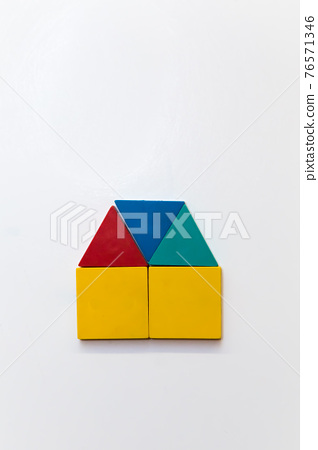 Small house of colorful figures on a white magnetic board. 76571346