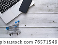 Top view of laptop, smartphone and cart on white wood background with copyspace for online shopping concept 76571549