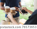 Asian Female client signing signature on digital tablet after receive hot drink from delivery man 76573653