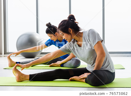 Two Asian women sporty attractive people practicing yoga lesson together 76573862