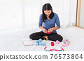 mother preparing baby clothes resting and relaxing on the bed 76573864