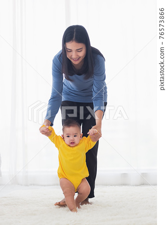 baby girl taking first steps learning to walk with mom 76573866