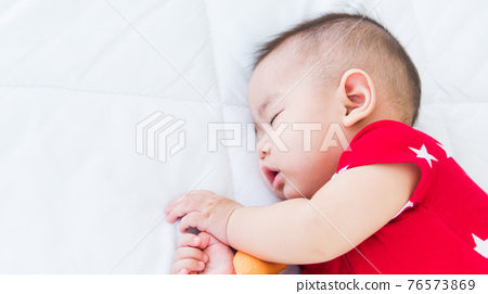 newborn little baby sleeping on white bed at home 76573869