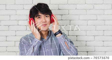 man standing with red headphones 76573870