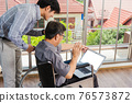 father man sitting wheelchair and his son talking video calls conference on laptop 76573872