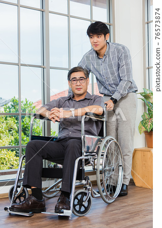 old man in a wheelchair and his young son 76573874
