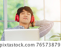 business man smile listening music in red headphone at home office 76573879