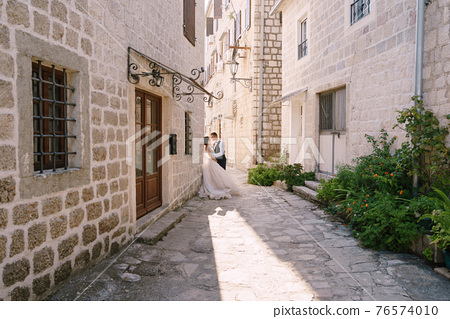 Wedding couple on the street of the old city, among ancient houses. Fine-art wedding photo in Montenegro, Perast. 76574010