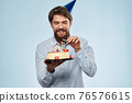 Bearded man with a plate of cake on a blue background and a birthday party hat on his head 76576615