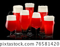 Set of fresh stout beer glasses with bubble froth isolated on black background. 76581420