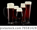 Set of fresh draft beer glasses with bubble froth isolated on black background. 76581428