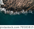 Top view of the blue sea with waves beating on beach and rocks. 76583815