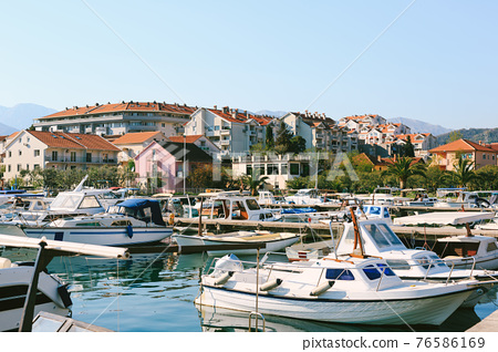 Boat pier in Tivat, Montenegro. Small fishing and pleasure boats are moored in the marina. 76586169