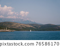 A white sailboat sails on the background of Mount Lovcen on blue water. 76586170