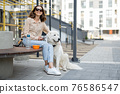 Woman sitting on bench with pet in the courtyard of the residence 76586547