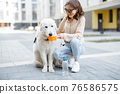 Woman gives a water in a bowl to her dog 76586575