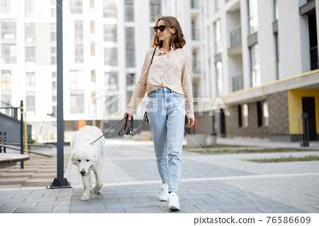 Woman walking with her big white dog on the street 76586609