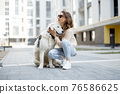 Woman walking with her big white dog on the street 76586625
