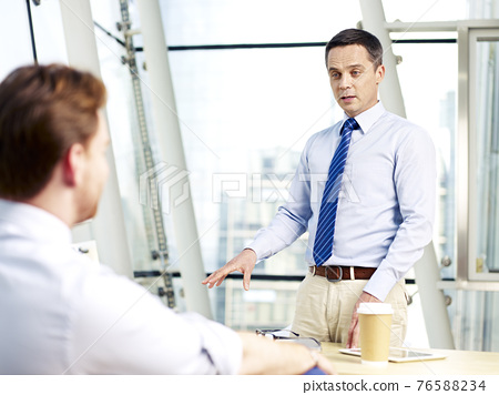 two caucasian corporate executives discussing business in office. 76588234