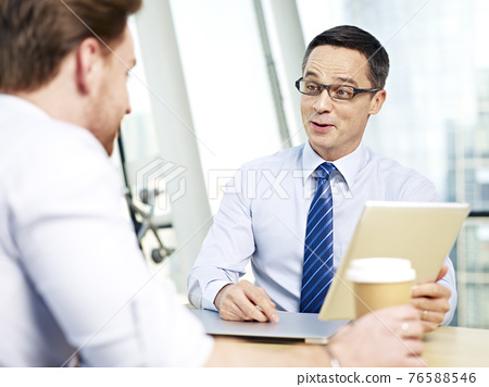 caucasian business man responding to coworker during a conversation in office 76588546