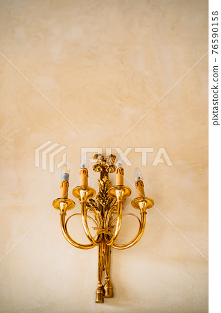 Gold sconce with four electric candles on the wall. Gold sconce vintage wall candles 76590158