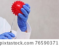 The dotctor's hands in disposable blue gloves hold an abstract model of the coronavirus and a syringe pointed in his direction. 76590371