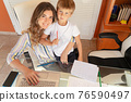 Mother working home with son 76590497