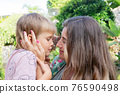 Mother playing with her son in garden 76590498