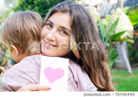 Mother playing with her son in garden 76590499