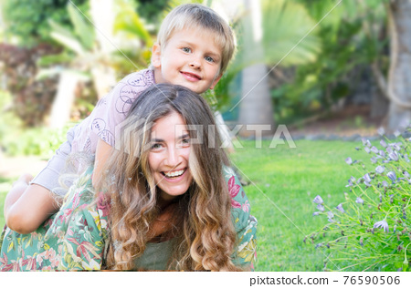 Mother playing with her son in garden 76590506