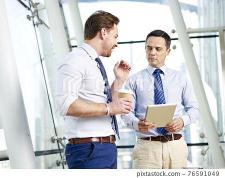 two caucasian businessperson having a serious discussion on business in office 76591049
