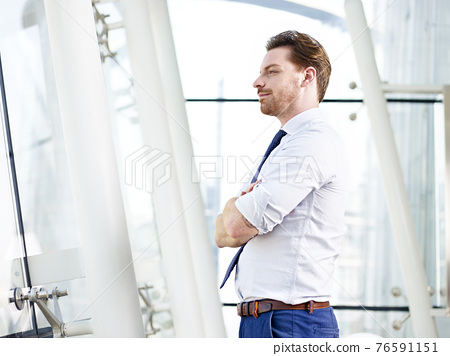 caucasian corporate person standing in office looking out of window thinking, arms crossed 76591151
